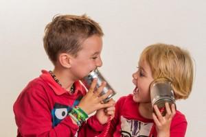 Zwei kleine Kinder telefonieren mit einem Telefon aus zwei Dosen.